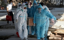 Several people are show wearing protective medical clothing and carrying a wooden casket.