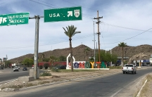 Street shot showing sign pointing to the USA, with a white truck driving down road, and colorful letters spelling Sonoyta, against backdrop of hills.