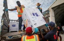 Men in orange and yellow jackets lift a box of vaccines from COVAX off of a truck bed