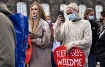 """A group of people protest and carry a heart-shaped sign that says """"Refugees welcome here."""""""