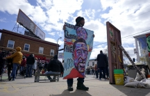 A man holds a sign at George Floyd Square, April 21, 2021, in Minneapolis, a day after former Minneapolis police Officer Derek Chauvin was convicted on all counts for the 2020 death of Floyd.