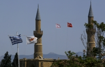 Greek and Cypriotflagsflutter on poles on the left, asTurkish and Turkish Cypriot breakaway flags fly between minarets on the right
