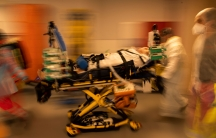 A COVID-19 patient is shown strapped to a yellow gurney with several medical staff moving along side in a blurred motion photograph.