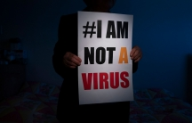"""A person is shown in shadow and holding a placard with """"#I am not a virus"""" printed on it."""