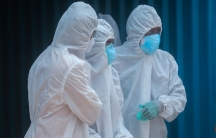 Three people wearing white biohazard suits look on to a dead relative out of frame