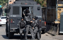 Several police officers are shown wearing dark colored fatigues and climbing out of a black armored vehicle carrying weapons.