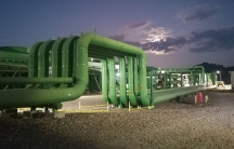 Huge green pipes on sandy ground against a dark blue sky