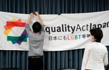 """A person is shown clipping a large banner with the words, """"Equality Act Japan"""" printed on it to a backdrop."""