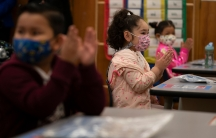 Children in pink and maroon jackets applaud in their classroom