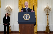 President Biden speaks at a podium while VP Harris stands to his right to listen