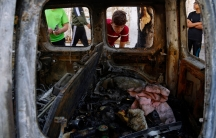 A child wearing a red short-sleaved shirt is shown looking into a bombed out and charred card.