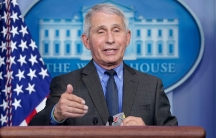 Dr. Fauci stands at a podium in the White House press room with the American flag over his shoulder