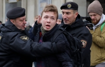 Raman Pratasevich is shown in a dark jacket with a police officer holding him on either side.