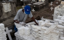 A man is shown wearing a blue hat and standing in front of dozens of white crosses while painting numbers on the crosses.