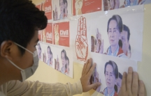 An anti-coup protester looks at the images of ousted Myanmar leader Aung San Suu Kyi during a protest against the military coup in Yangon, Myanmar, on April 26, 2021.