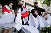Several people are shown wearing protective face masks and standing behind a red string with several folded paper airplanes attached.