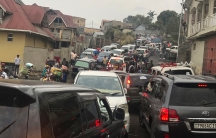 Dozens of cars are shown from behind packed into a road trying to drive out of Goma with houses on either side.