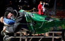 Man with oxygen mask lies face down on a stretcher with a green blanket on top and two people in the distance