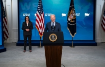 Vice President Kamala Harris is shown standing several feet behind President Joe Biden who is standing at a wooden podium.