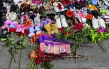Flowers, children's shoes and other items rest at a memorial