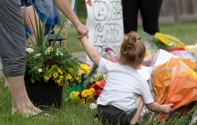 A woman holds on to a child's hand and she places flowers at a memorial