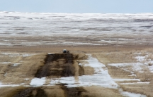 Wide shot of snowy barren land with a white car parked in the middle