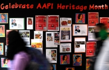 People walk past a board full of pictures celebrating AAPI heritage month