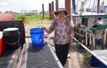 A woman wearing a hat stands next to a blue bucket