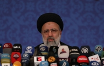 Iranian President Ebrahim Raisi is shown behind a large number of microphones.