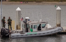 """Three men in green suits stand on a small boat that says """"Border Patrol"""" with an American flag in the middle"""