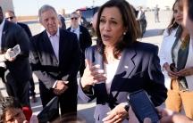 Vice president Kamala Harris, in a blue suit, speaks to reporters