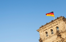 Black, red and yellow German flag waves on top of a building