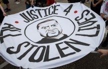 """Hands hold a round white cloth circle with George Floyd's face in the middle that reads, """"Justice 4 all stolen lives"""""""
