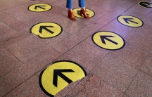 Several large stickers are shown on the floor with yellow and black arrows with a person standing on one arrow going the opposite direction.
