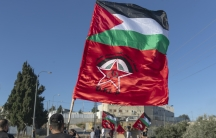Palestinian protesters fly Palestinian flags and flags of the Democratic Front for the Liberation of Palestine, DFLP, during clashes with Israeli soldiers at the entrance the Jewish settlement of Beit El, background near the West Bank city of Ramallah.