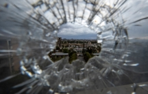 A circular hole is shown in a in a glass windown with cracks radiating from the center and through the hole buildings can be seen.