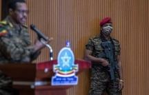 Lieutenant-General Bacha Debele is show standing at a podium with his hand raised in soft focus with a guard in military fatigues is shown in focus and holding a large rifle.
