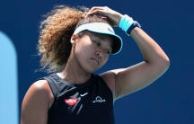 Naomi Osaka, in a tennis hat and ponytail, puts her hand on her head