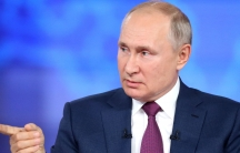 Russian President Vladimir Putin is shown wearing a blue suit and purple tie while pointing with his right hand.