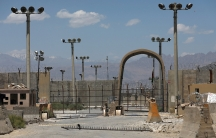 Several tall lamp posts are shown with an arched stone gate with fencing and barbed wire.