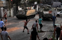 Several people are shown in a street throwing items at a tank and other armored vehicles.