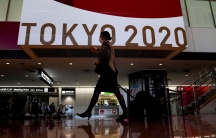 A woman is shown walking and pulling a rollaboard in an airport terminal with the Tokyo Olympics 2020 sign in the background.