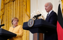 President Joe Biden and German Chancellor Angela Merkel are shown each standing behind podiums with several microphones on each stand.