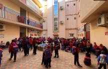 A large crowd of young students are shown wearing backpacks and walking in a courtyard with tan-colored buildings on three sides.