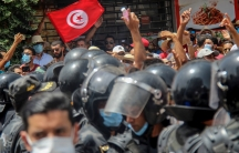 A crowd of people are shown being pushed back by a row of black helmet-clad police officials.
