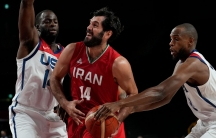 Two basketball players dressed in white US uniforms are shown on either side of a player wearing a red Iranian uniform.
