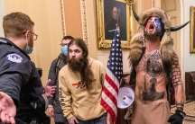 Supporters of President Donald Trump, including Jacob Chansley, right with fur hat, are confronted by USCapitol Police officers outside the Senate Chamber inside the Capitol in Washington. Many of those who stormed the Ca