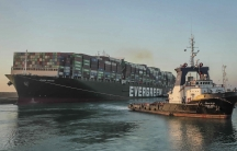 Large container ship being pulled by a tugboat