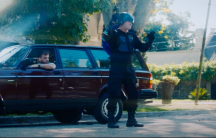 A man dressed as a superhero stands outside near a car.