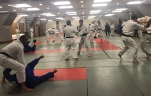A group of 40 men of all ages wear a mix of white and blue judogis —the traditional judo uniform. Most are black belts.